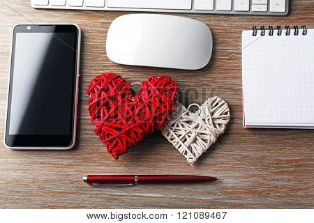 Computer peripherals with hearts, notebook and mobile phone on wooden table