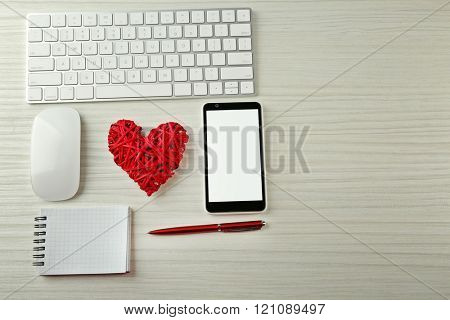 Computer peripherals with wicker red heart, notebook and mobile phone on light wooden table