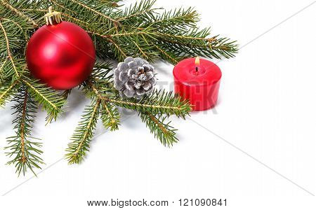 The branch of spruce red ball cones and red candle