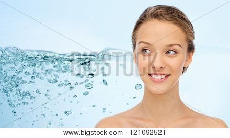 beauty, people and health concept - smiling young woman face and shoulders over water splash on blue background