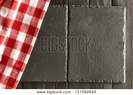Empty slate plates and tablecloth over black wooden background
