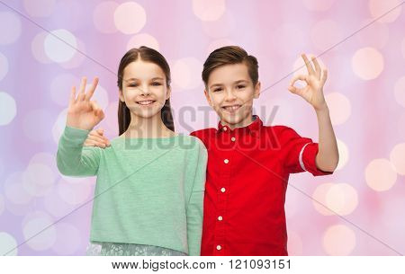 childhood, fashion, gesture and people concept - happy smiling boy and girl hugging and showing ok hand sign over pink holidays lights background
