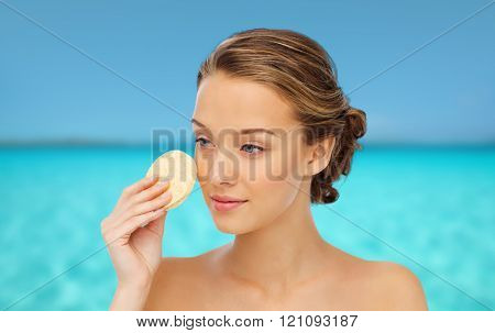 beauty, people and skincare concept - young woman cleaning face with exfoliating sponge over blue sea and sky background