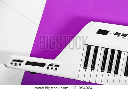 Keyboard of synthesizer on purple background