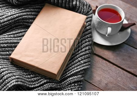 A book, a cup of tea and a woolen blanket on wooden background