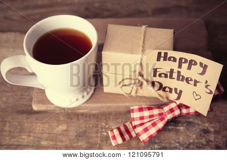 Greeting card for Happy Father's Day with tea cup, gift box and bow tie on wooden background