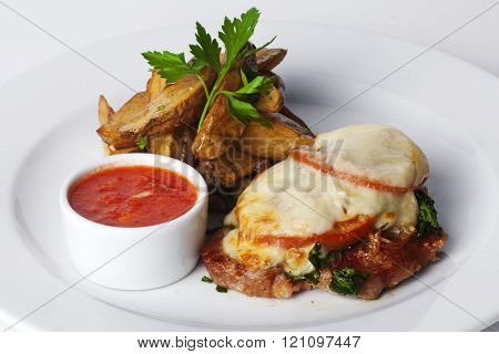 beef, pork, veal, roasted meat with tomatoes and mayonnaise, potato wedges in the peel on a plate is