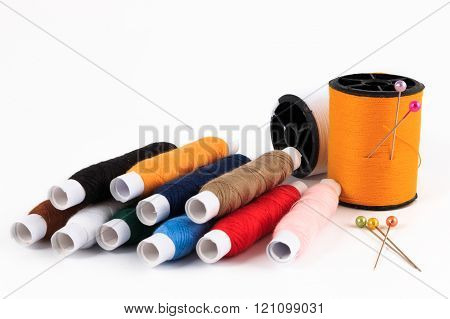 Spool of thread with needle, colorful sewing bobbin thread isolated on white.