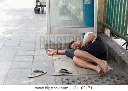 BANGKOK - Mar 8: An unidentified man sleeps on the street in city centre on Mar 8, 2016 in Bangkok, Thailand. The government estimates 4,000 homeless in Bangkok while NGOs put the figure far higher