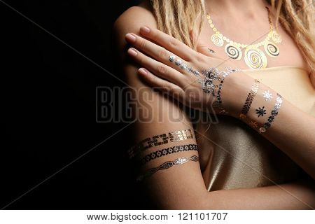Young blonde girl with golden and silver flash tattoo on black background