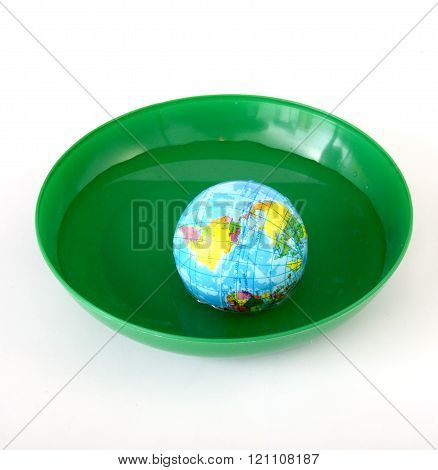 Picture of a Globus toy ball in a green plastic plate with water
