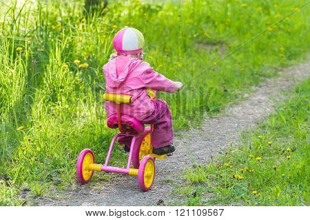 Back view full length portrait of little girl riding kids pink and yellow tricycle on park track