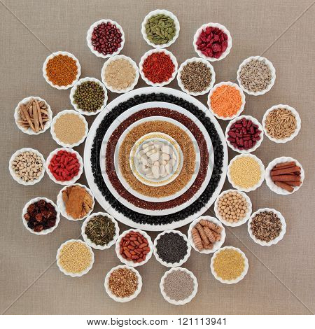 Dried health food in china bowls forming an abstract wheel design over hessian background. Foods high in minerals, vitamins, antioxidants and dietary fiber.