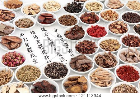Chinese herbal medicine ingredients with calligraphy on rice paper. Translation reads as chinese herbal medicine as increasing the bodys ability to maintain body and spirit health and balance energy.