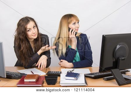 The Situation In The Office - One Employee On The Phone, The Other Asks For Her Phone