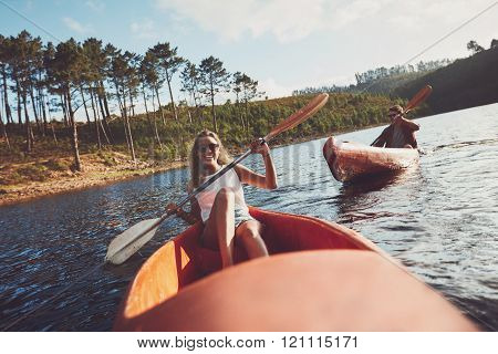 Happy Kayakers Rowing On A Lake