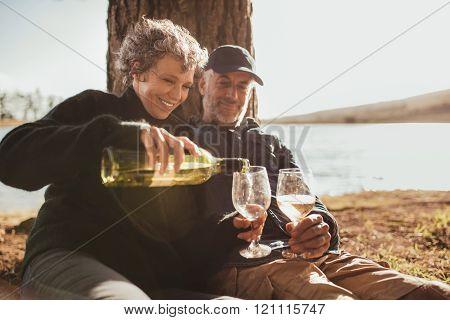 Senior Couple Enjoying Drinks At Campsite Near Lake