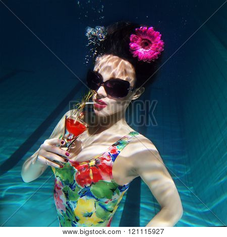 beautiful girl in a colorful stylish swimsuit and sunglasses and pink gerbera in the head with a coc