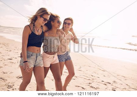 Young Friends Walking Along A Beach During Summertime