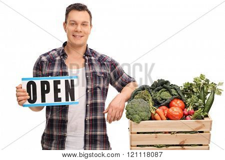 Young market vendor holding an open sign next to a crate full of vegetables isolated on white background