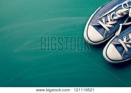 vintage sneakers on green chalkboard