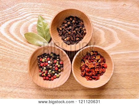 Wooden bowls with pepper, clove and paprika.