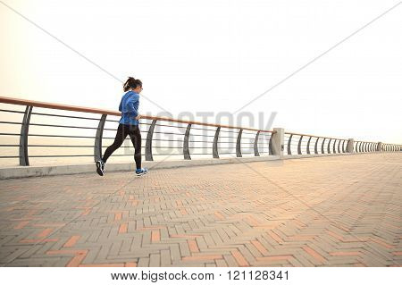 young fitness woman runner running on seaside road
