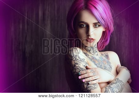 Beautiful young woman with stylish crimson hair and tattoo on her body posing over dark grunge background. Hair coloring. Cosmetics, make-up. Tattoo.