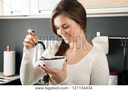 Woman With Bowl Of Coco Cereal In Kitchen