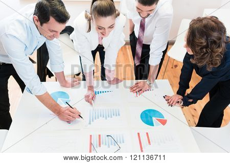 Financial consultants in bank analyzing data and discussing graphs