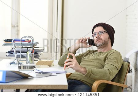 corporate portrait of young hipster businessman working from modern home office as freelancer wearing casual beanie talking on mobile phone in creative freestyle business people
