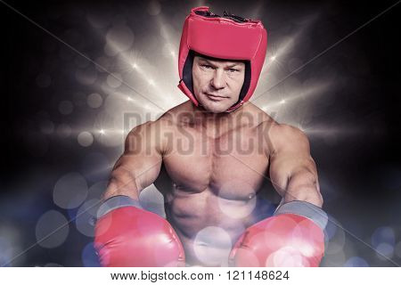 Portrait of boxer with red gloves and headgear against spotlight