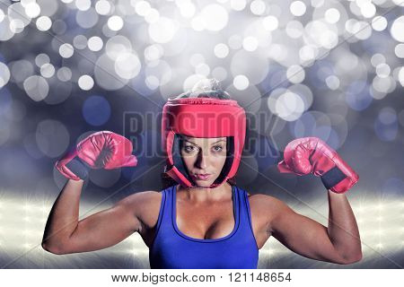 Portrait of female fighter with gloves and headgear against spotlight