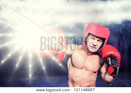Boxer punching against black background against red boxing area with punching bags