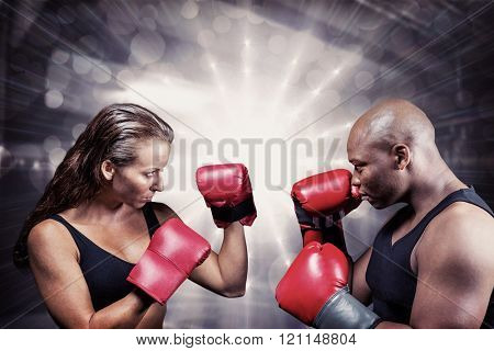 Athletes with fighting stance against red boxing area with punching bags