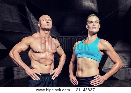 Muscular man and woman with hand on hip against black angular design