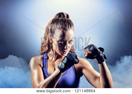 Portrait of female confident boxer with fighting stance against cloudy sky