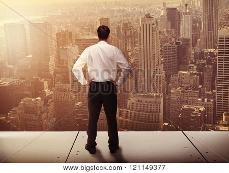 Rear view of classy young businessman posing against view of cityscape
