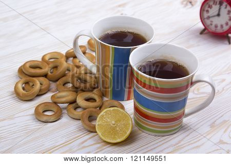 Two cups for tea with fragrant bagels on  wooden background