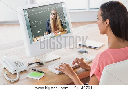 Businesswoman using computer at desk in creative office against green
