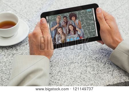 Businessman holding small tablet at table against green