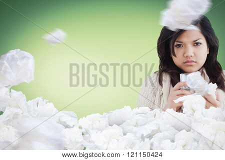 Sick woman holding a tissue and a glass of water against used tissues