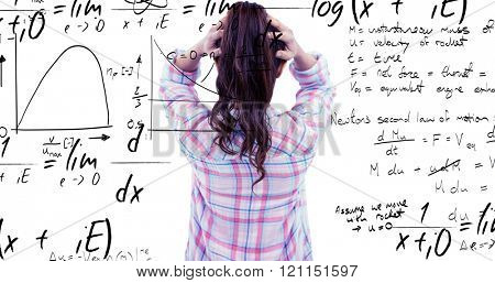 Brunette with hands on hair in front of sticky notes on wooden wall against maths equation