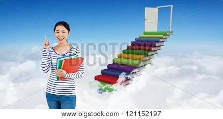 Cheerful woman pointing up while holding files against steps made from books leading to open door