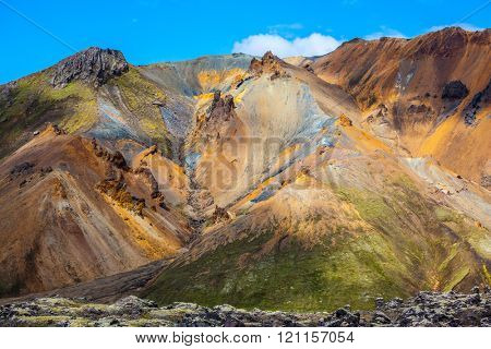 Travel to Iceland in the July. Summer volcanic tundra. Multi-colored mountains from mineral rhyolite are lit with sun