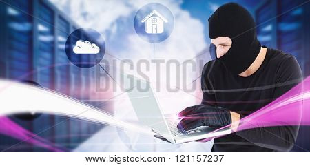 Focused burglar standing holding laptop against abstract lines on black background