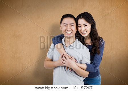 Portrait of cheerful couple against orange background