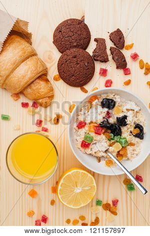 Top view of bowl with oat flackes, croissant, cookies and fresh juice in a mess on the table