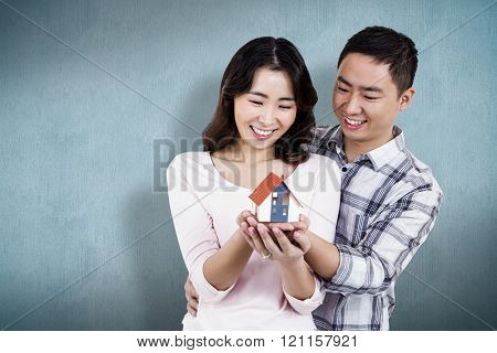 Happy couple holding a model house against blue background