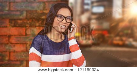 Asian woman on a phone call against wall of a house